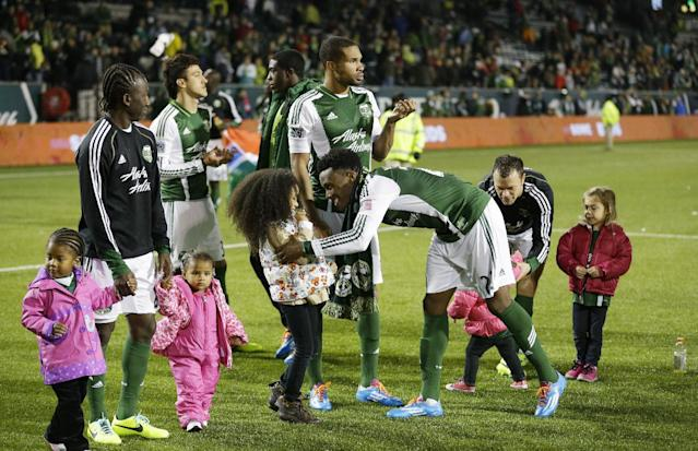 Portland Timbers players, including Rodney Wallace, center, celebrate with family members after the Timbers beat the Seattle Sounders 3-2 in the second game of the Western Conference semifinals in the MLS Cup soccer playoffs, Thursday, Nov. 7, 2013, in Portland, Ore. The win gave the Timbers a 5-3 aggregate score in the two-match series. The Timbers will advance to the Western Conference semifinals against Real Salt Lake. (AP Photo/Ted S. Warren)