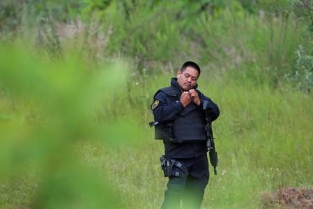 A police officer keeps watch near a clandestine grave while officials resumed the search for human remains after authorities found bodies packed in plastic bags, in the municipality of Zapopan
