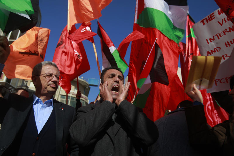Palestinian protesters waving national and Popular Front for the Liberation of Palestine flags chant slogans during a demonstration against U.S. Secretary of State John Kerry in the West Bank city of Ramallah, Wednesday, Jan. 15, 2014. (AP Photo/Majdi Mohammed)