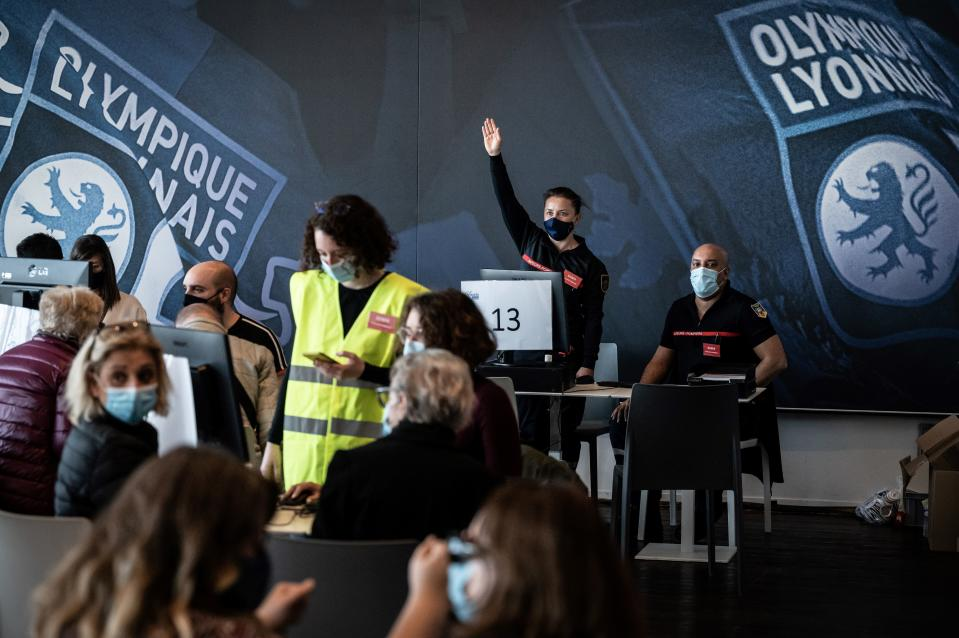 Firefighters welcome people to be vaccinated against Covid-19 on the opening day of a mass vaccination centre set up in the Olympique Lyonnais soccer Stadium, in Decines-Charpieu, Saturday, April 3, 2021. (Jean-Philippe Ksiazek, Pool via AP)