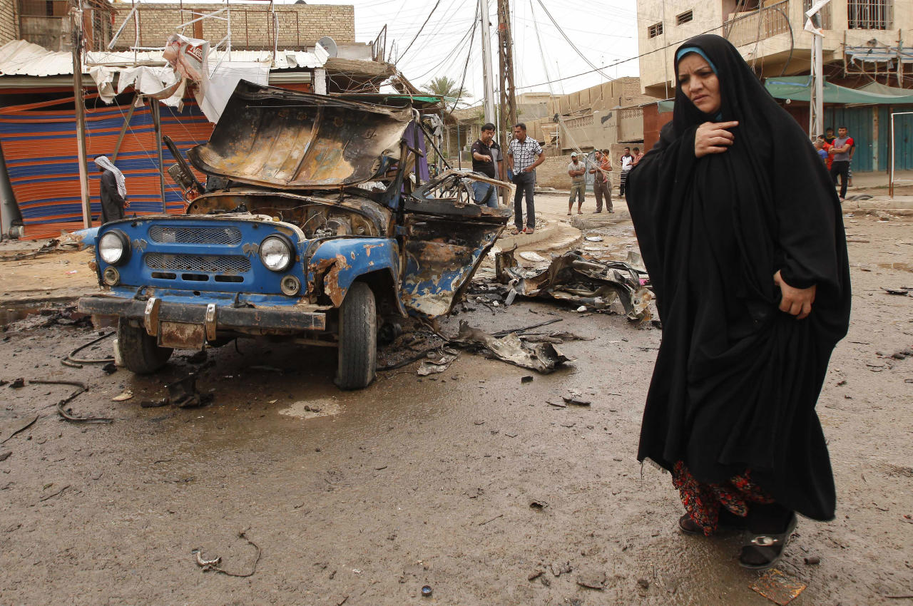 An Iraqi woman passes by the scene of a car bomb attack in Kamaliyah neighborhood, a predominantly Shiite area of eastern Baghdad, Iraq, Monday, May 20, 2013. A wave of car bombings across Baghdad's Shiite neighborhoods and in the southern city of Basra killed and wounded dozens of people, police said. (AP Photo/ Hadi Mizban)