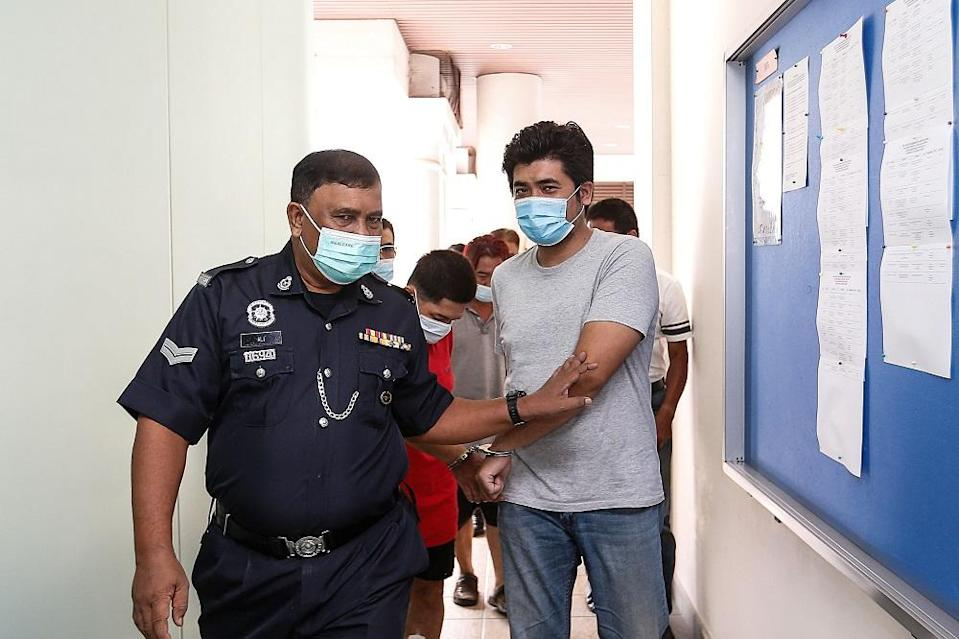 Muhammad Aslam Hashim is escorted by a policeman at the Magistrate's Court in George Town April 23, 2021. ― Picture by Sayuti Zainudin