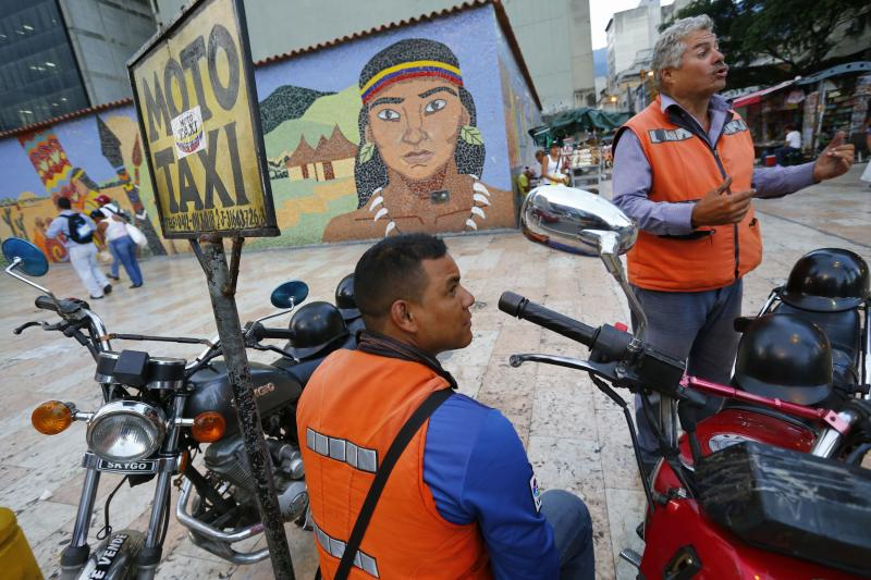 Motorcycle taxi drivers wait for customers in downtown Caracas