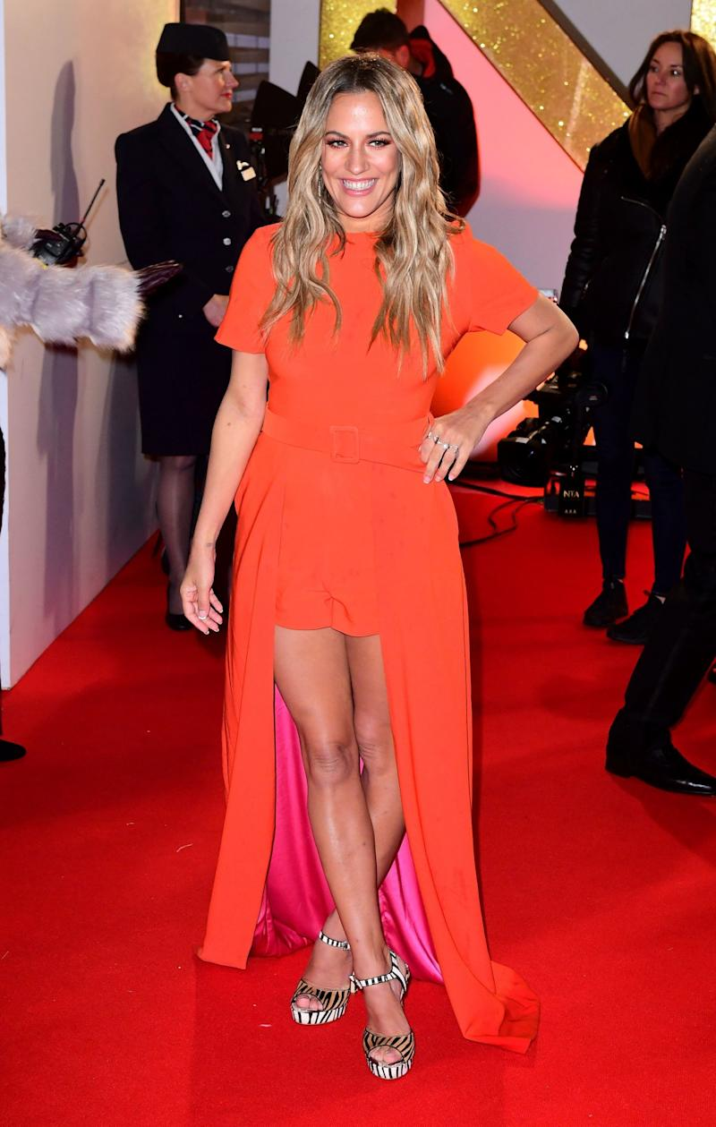 Pose: Caroline Flack stunned in orange on the red carpet (Ian West/PA Wire)