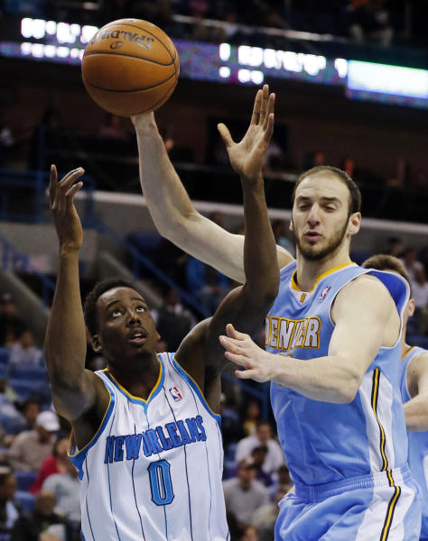 New Orleans Hornets forward Al-Farouq Aminu (0) and Denver Nuggets center Kosta Koufos (41) reach for a loose ball in the first half of an NBA basketball game in New Orleans, Monday, March 25, 2013. (AP Photo/Bill Haber)