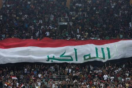 A Iraqi flag is held by fans during the game of the West Asia Football Federation Championship between Iraq and Lebanon in the holy city of Kerbala