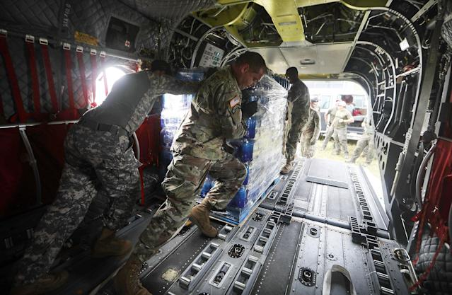 <p>U.S Army soldiers offload bottled water from a helicopter during recovery efforts four weeks after Hurricane Maria struck on Oct. 18, 2017 in Utuado, Puerto Rico. U.S. soldiers and agents delivered food and water provided by FEMA to remote residents in mountainous Utuado. (Photo: Mario Tama/Getty Images) </p>