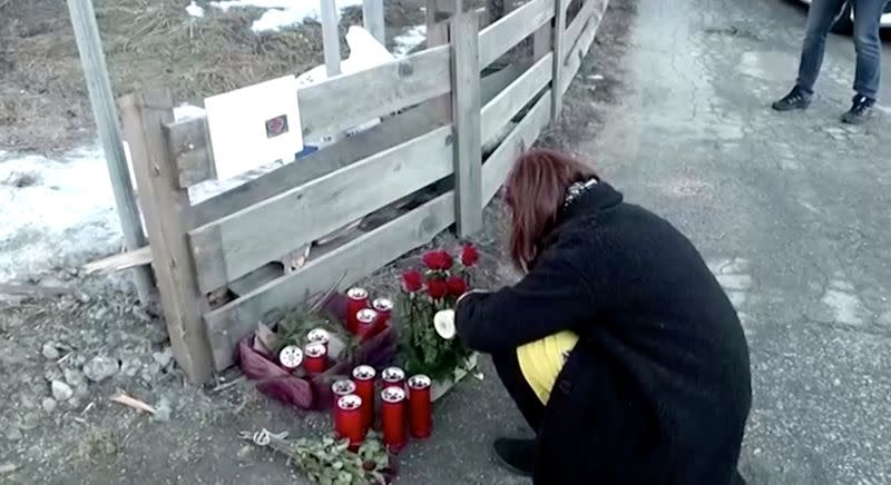 A woman lights a candle after a suspected drunk driver fatally struck a group of German tourists in Lutago