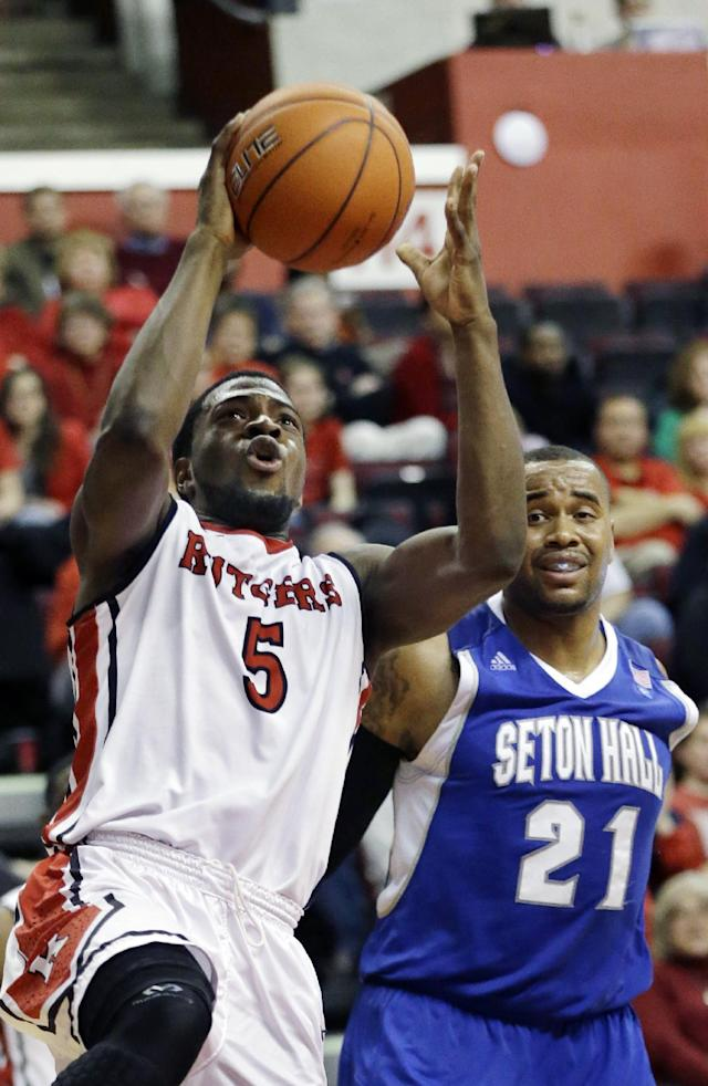 Rutgers' Eli Carter (5) shoots past Seton Hall's Gene Teague (21) during the second half of an NCAA college basketball game on Tuesday, Feb. 12, 2013, in Piscataway, N.J. Carter had 14 points in Rutgers' 57-55 win. (AP Photo/Mel Evans)