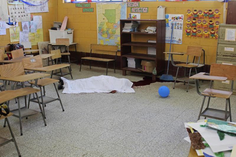 A sheet covers the body of elementary school student Juan Armando Coy Cal, 13, in the classroom where he was killed at his public school in San Juan Tactic, north of Guatemala City, Wednesday, Sept. 12, 2012.  Interior Minister Mauricio Lopez Bonilla says Julio Saquil was drunk when he entered an elementary school in the northern province of Alta Verapaz on Wednesday and slit the throats of two children with a machete. Bonilla says a mob then set the 35-year-old man on fire in the school's patio and he burned to death.  (AP Photo)