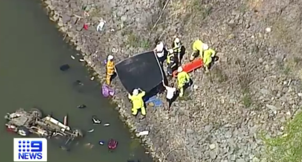 Emergency services at the scene of the Wyaralong Dam, holding up a tarp with a stretcher standing by and a flipped car in the water.