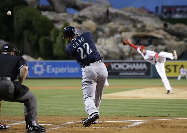Seattle Mariners' Robinson Cano hits a fly ball off of Los Angeles Angels starting pitcher C.J. Wilson during the first inning of a baseball game on Tuesday, April 1, 2014, in Anaheim, Calif. (AP Photo/Jae C. Hong)
