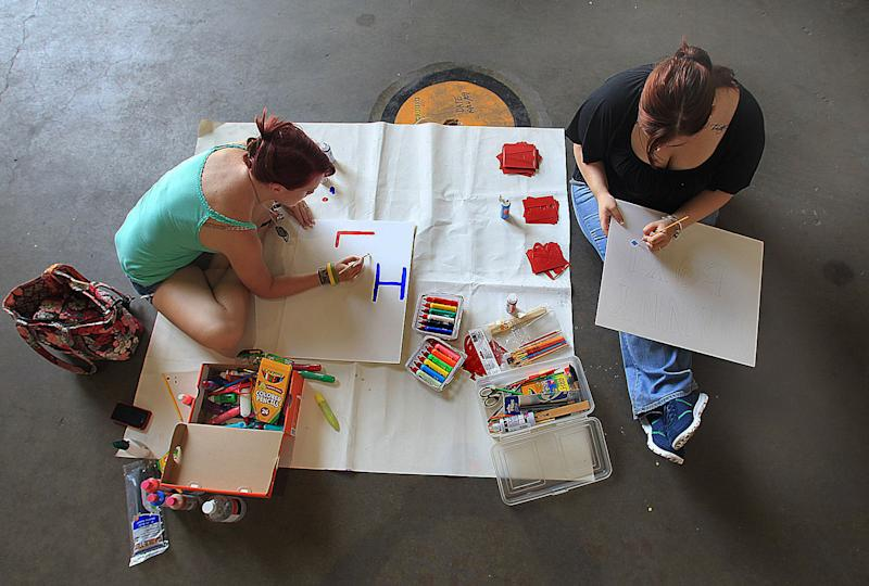 In this Saturday, July 28, 2012 photo, Selina Milton, left, and Courtnie Schumacher work on their posters for the homecoming and return of their husbands, Lance Cpl. Kenny Milton and Lance Cpl. Daniel Schumacher, during a banner-making party at a hangar at New River Air Station near Camp Lejeune in Jacksonville, N.C. Families and friends will hang large sheets and banners on a fence outside the base to welcome home Marines from Afghanistan and Iraq, and wave posterboard signs as they wait for their arrival. (AP Photo/Chuck Beckley)