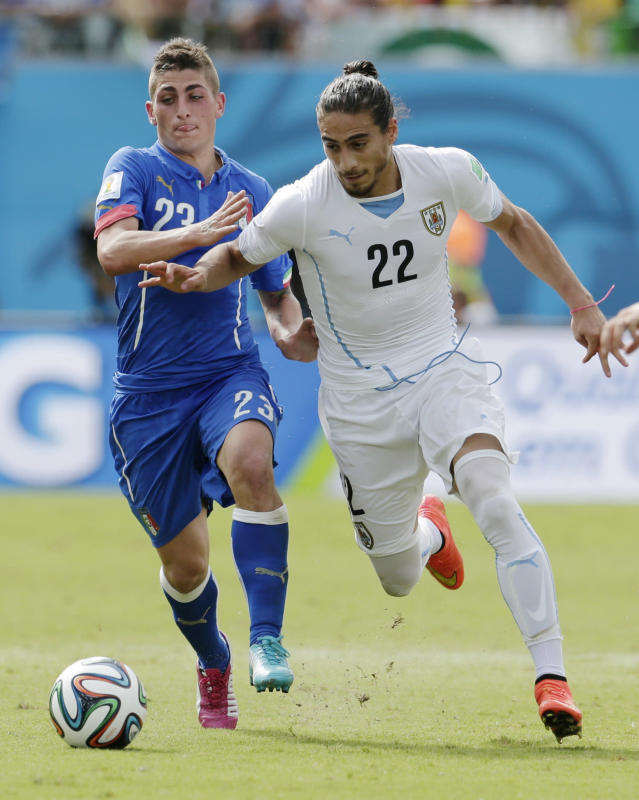 Uruguay's Martin Caceres attacks while being chased by Italy's Marco Verratti during the group D World Cup soccer match between Italy and Uruguay at the Arena das Dunas in Natal, Brazil, Tuesday, June 24, 2014. (AP Photo/Petr David Josek)