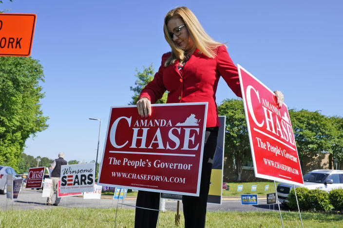 Republican gubernatorial candidate State Sen. Amanda Chase, places a yard sign during a drive through GOP Convention vote in Chesterfield, Va., Saturday, May 8, 2021. (AP Photo/Steve Helber)