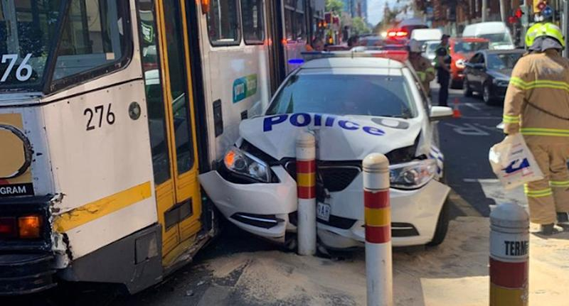 A smashed Victoria Police car sits next to a tram after a crash in Melbourne's CBD.