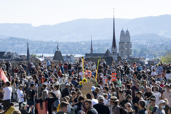 People hold banners and gather to rally against global warming and climate change in Zurich, Switzerland, Friday Sept. 24, 2021. (Ennio Leanza/Keystone via AP)