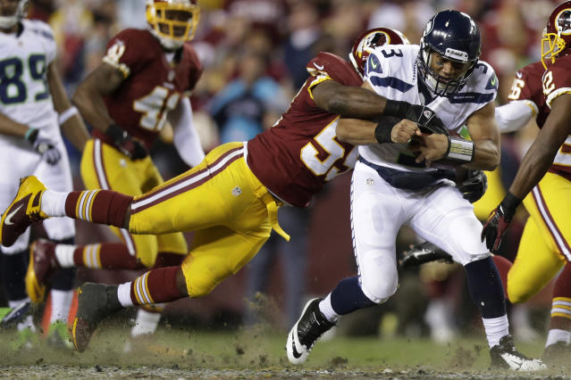 Seattle Seahawks quarterback Russell Wilson is stopped by Washington Redskins inside linebacker London Fletcher during the first half of an NFL wild card playoff football game in Landover, Md., Sunday, Jan. 6, 2013. (AP Photo/Evan Vucci)