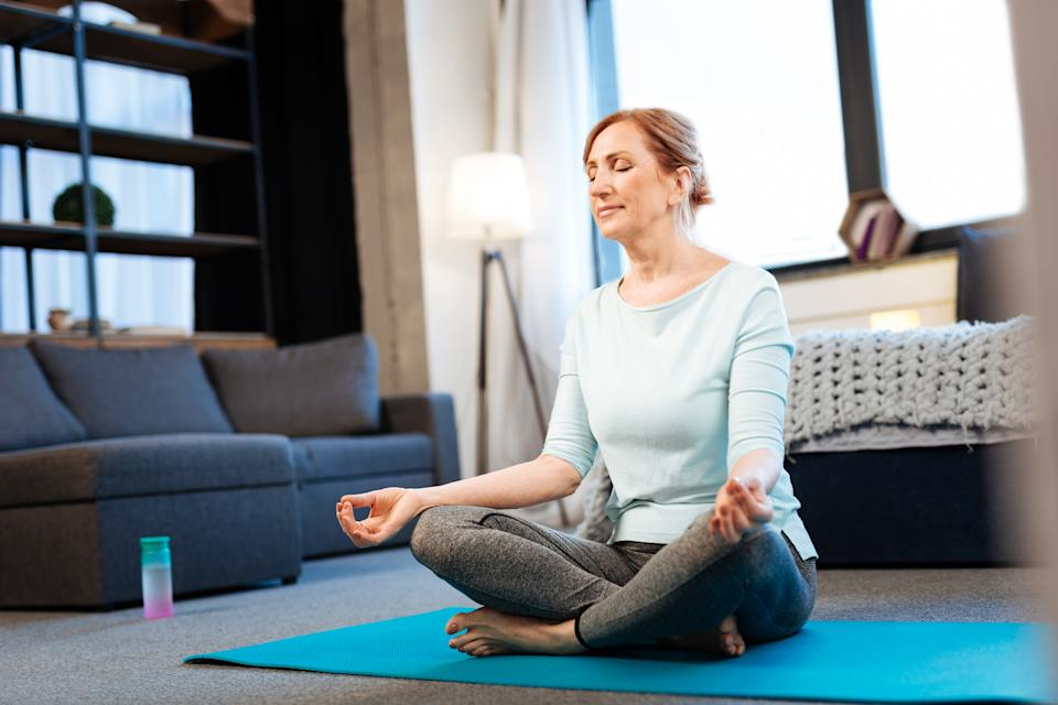 Morning meditation. Tranquil good-looking woman meditating with closed eyes while having connected fingertips
