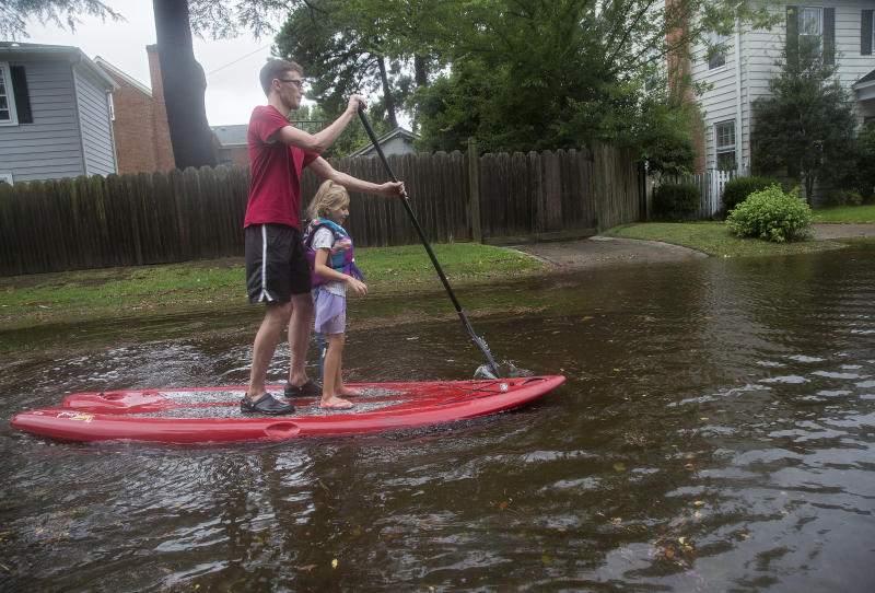 Eric Young stand-up paddleboards through flooded streets in Larchmont with his daughter, Emily Ruth, 5, after Hurricane Dorian brought heavy wind and rain to Norfolk, Va., on Friday, Sept. 6, 2019. (Kaitlin McKeown/The Virginian-Pilot via AP)
