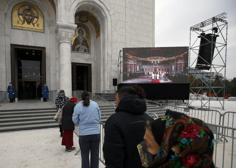 Believers stand in front of St. Sava Temple during the funeral procession of Patriarch Irinej in Belgrade, Serbia, Sunday, Nov. 22, 2020. The 90-year-old Irinej died early on Friday, nearly three weeks after he led the prayers at a funeral of another senior church cleric in neighboring Montenegro, who also died after testing positive for the virus. (AP Photo/Darko Vojinovic)