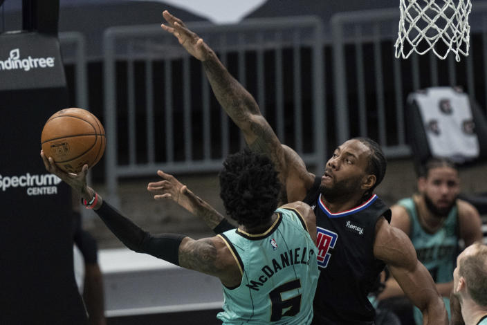 Charlotte Hornets forward Jalen McDaniels (6) drives to the basket while guarded by Los Angeles Clippers forward Kawhi Leonard during the first half of an NBA basketball game in Charlotte, N.C., Thursday, May 13, 2021. (AP Photo/Jacob Kupferman)