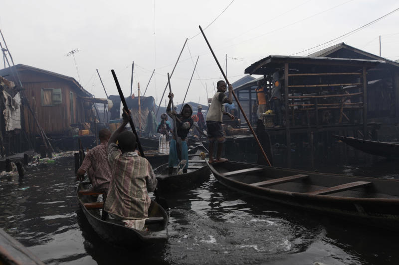People travel on a canoe at the floating slum of Makoko in Lagos, Nigeria, Thursday, Sept. 27, 2012. A group is planning to build a floating school in the slum, which state authorities have targeted for demolition in the past. (AP Photo/Sunday Alamba)