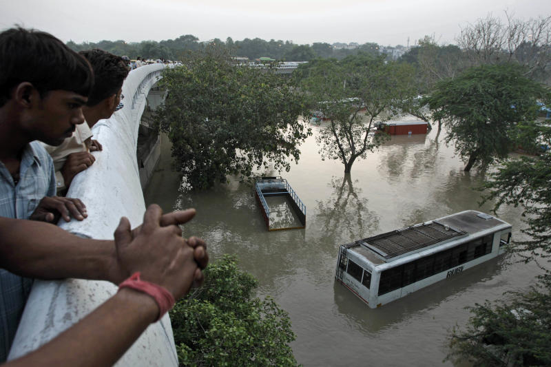 People gather to look at submerged buses and trucks in the rising Yamuna River as they stand on a flyover in New Delhi, India, Wednesday, June 19, 2013. India's prime minister said Wednesday that the death toll from flooding this week in the northern state of Uttrakhand had surpassed 100 and could rise substantially. The flooding has affected several states and the capital New Delhi where nearly 2,000 people have been evacuated to government-run camps on higher ground. Authorities there said the situation would ease as the level of the Yamuna River was expected to start receding Thursday afternoon. (AP Photo/Tsering Topgyal)