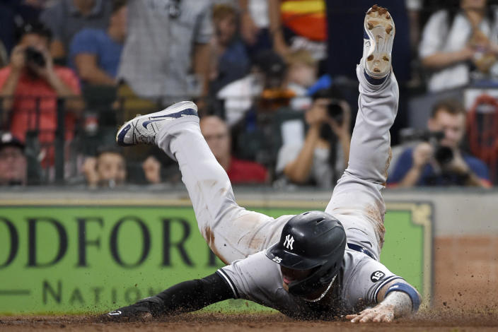 New York Yankees' Gleyber Torres slides past home plate to score during the seventh inning of a baseball game against the Houston Astros, Sunday, July 11, 2021, in Houston. (AP Photo/Eric Christian Smith)