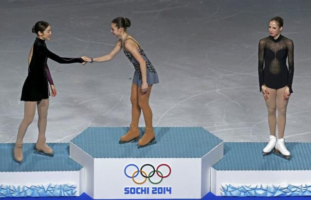 First-placed Russia's Adelina Sotnikova (C) shakes hands with second-placed South Korea's Kim Yuna (L) as third-placed Italy's Carolina Kostner looks on, on the podium after the figure skating women's free skating program at the 2014 Sochi Winter Olympics, February 20, 2014. REUTERS/Issei Kato (RUSSIA - Tags: OLYMPICS SPORT FIGURE SKATING TPX IMAGES OF THE DAY)