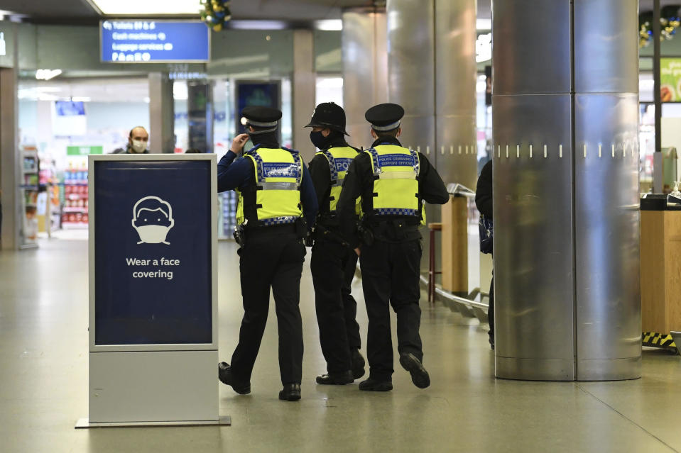 Police officers at St Pancras, with more being deployed to enforce travel rules at London's stations, after Britian's Prime Minister Boris Johnson introduced Tier 4 restrictions for London and the south east of the country, in London, Sunday, Dec. 20, 2020. Millions of people in England have learned they must cancel their Christmas get-togethers and holiday shopping trips. British Prime Minister Boris Johnson said Saturday that holiday gatherings can't go ahead and non-essential shops must close in London and much of southern England. Johnson imposed a new, higher level of coronavirus restrictions to curb sharply spreading infections in the capital and other areas. (Stefan Rousseau/PA via AP)