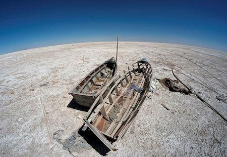 Boats are seen on the dried lake Poopo affected by climate change, in the Oruro Department