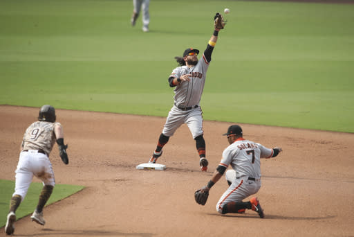 San Francisco Giants shortstop Brandon Crawford, top, cannot field a throw by Donovan Solano (7) on a ground ball hit by San Diego Padres' Greg Garcia in the sixth inning of a baseball game Sunday, Sept. 13, 2020, in San Diego. Austin Nola scored on the play while Croneworth was safe at second and advanced to third on the throwing error by Solano. (AP Photo/Derrick Tuskan)