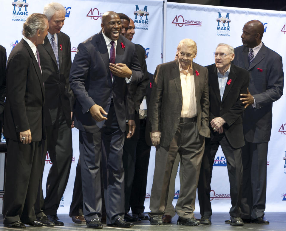 FILE - In this Nov. 7, 2011 file photo, Los Angeles Lakers owner Jerry Buss, third from right, looks towards Magic Johnson, third from left, during a ceremony of the Magic Johnson Foundation in Los Angeles. Also shown are former Lakers team members Pat Riley, left, Mitch Kupchak, second from left, Bill Sharman, second from right, and James Worthy, right. Buss, the Lakers' playboy owner who shepherded the NBA franchise to 10 championships, has died. He was 80. Bob Steiner, an assistant to Buss, confirmed Monday, Feb. 18, 2013 that Buss had died in Los Angeles. Further details were not available.(AP Photo/Damian Dovarganes, FIle)