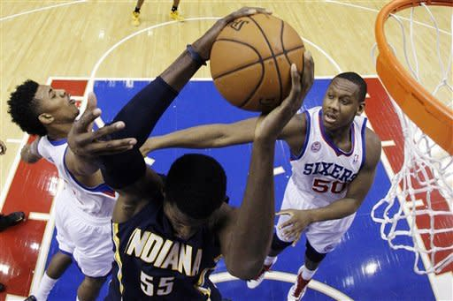 Indiana Pacers' Roy Hibbert, center, pulls in a rebound between Philadelphia 76ers' Nick Young, left, and Lavoy Allen during the first half of an NBA basketball game, Wednesday, Feb. 6, 2013, in Philadelphia. (AP Photo/Matt Slocum)