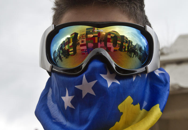 """A Kosovo Albanian youth wearing ski goggles and a Kosovo flag stands near the """"NEWBORN"""" monument painted with flags of the countries that have recognized Kosovo's independence marking the 5th anniversary since Kosovo seceded from Serbia in capital Pristina on Sunday, Feb. 17, 2013. Serbia rejects Kosovo independence. (AP Photo/Visar Kryeziu)"""
