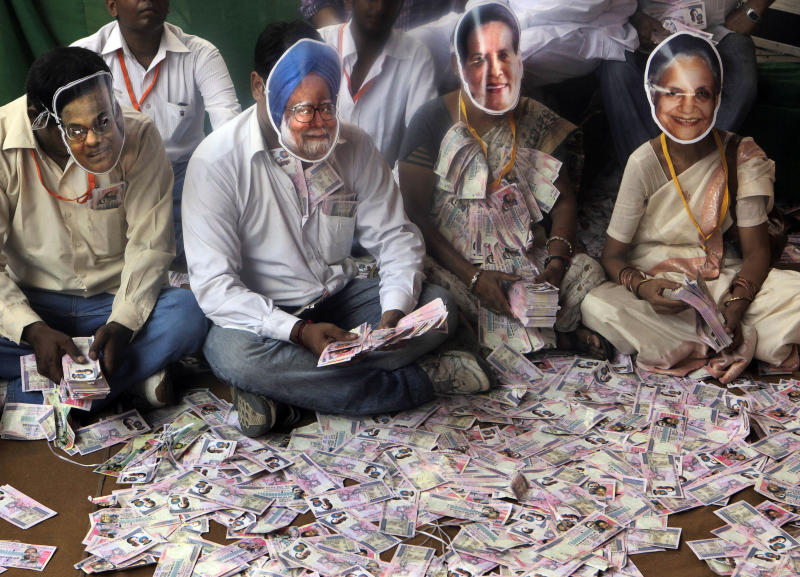 India's main opposition Bharatiya Janata Party activists wear masks, from left, Indian Home Minister P. Chidambaram, Prime Minister Manmohan Singh, Congress party President Sonia Gandhi, and Delhi Chief Minister Sheila Dikshit with fake currency notes in hands during a rally against growing corruption cases under the ruling United Progressive Alliance, in  New Delhi, India, Tuesday, Aug. 9, 2011. Thousands of BJP supporters are marching in New Delhi to protest against the Congress party-led government's hosting of last year's Commonwealth Games. Auditors slammed India's preparations and conduct of the Commonwealth Games last year as deeply flawed, riddled with favoritism and vastly more expensive than planned in a final report that could result in criminal prosecutions. (AP Photo/Manish Swarup)