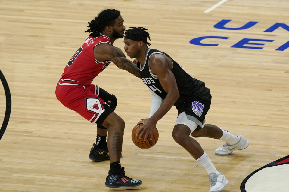 Sacramento Kings guard Buddy Hield, right, drives against Chicago Bulls guard Coby White during the first half of an NBA basketball game in Chicago, Saturday, Feb. 20, 2021. (AP Photo/Nam Y. Huh)