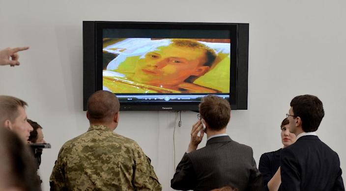 Journalists and an officer watch a video allegedly showing a Russian soldier, captured in the separatist Lugansk region of Ukraine, before a press conference in the Ministry of Defence of Ukraine in Kiev on May 18, 2015 (AFP Photo/Genya Savilov)