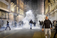 Smoke billows as clashes broke out during a protest against the government restriction measures to curb the spread of COVID-19 in Turin, Italy, Monday, Oct. 26, 2020. Protesters turned out by the hundreds in Italian several cities and towns on Monday to vent anger, sometimes violently, over the latest anti-COVID-19 rules, which force restaurants and cafes to close early, shutter cinema, gyms and other leisure venues. In the northern city of Turin, demonstrators broke off from a peaceful protest and hurled smoke bombs and bottles at police in the city square where the Piedmont regional government is headquartered. (Claudio Furlan/LaPresse via AP)