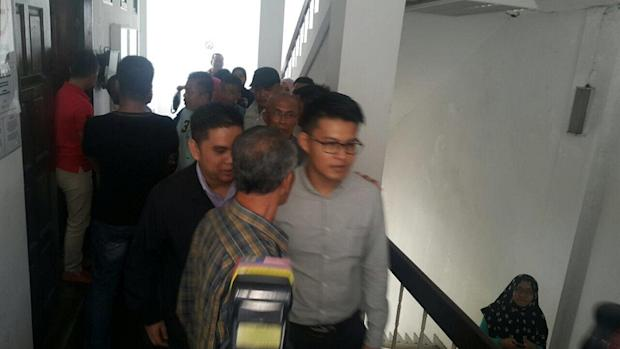 Inspector Mohd Faiz Mohd Yusof (centre, in glasses) being brought to court to be charged for accepting bribes amounting to RM3,000 in a Narcotics case in Penampang, Sabah March 9, 2017.