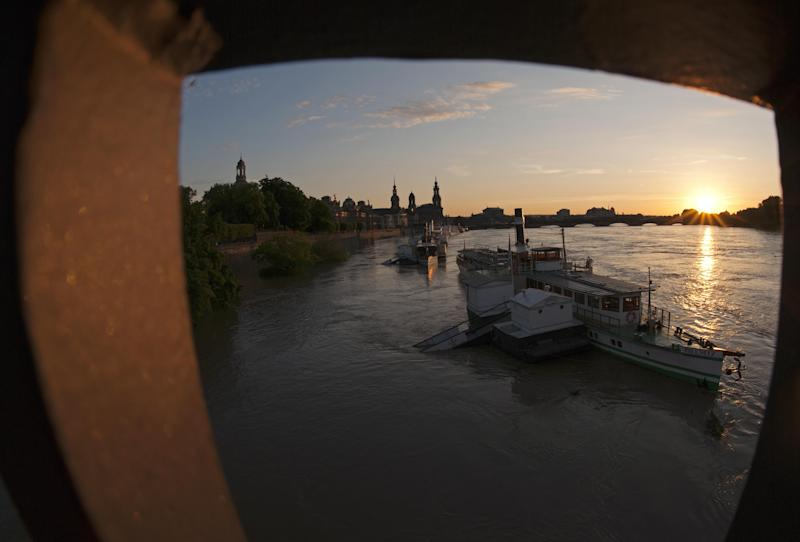 The sun goes down behind the flooded landing stages of the steamers by river Elbe in the old town of Dresden, eastern Germany, Wednesday, June 5, 2013. Heavy rainfalls cause flooding along rivers and lakes in Germany, Austria, Switzerland and the Czech Republic. (AP Photo/Jens Meyer)
