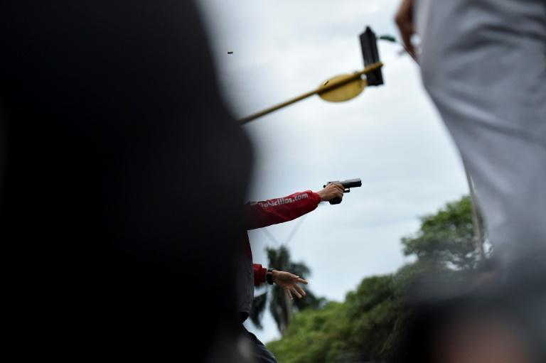 A man fires a gun during a clash between demonstrators and police on May 28, 2021