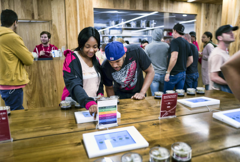 FILE - In this May 19, 2018 photo tourists Randy Wilkie and Keya Cole from Buffalo, New York, check out the offerings of cannabis at one of the MedMen cannabis dispensaries in Los Angeles, prior to boarding the Green Line Trips bus tour. California's struggling legal cannabis industry is expected to grow next year to $3.1 billion, but it remains far outmatched by the state's thriving illegal market. A report released Thursday, Aug. 15, 2019, finds consumers are spending roughly $3 in the state's underground pot economy for every $1 in the legal one. (AP Photo/Richard Vogel,File)