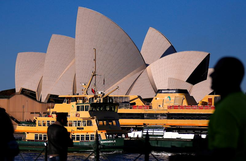 Pedestrians and passengers aboarding ferries can be seen in front of the Sydney Opera House in central Sydney, Australia July 30, 2018. REUTERS/David Gray