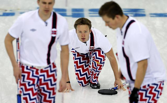 Norway's Torger Nergaard, center, looks at the rock while his teammates Haavard Vad Petersson, left, and Christoffer Svae, right, sweep the ice during the men's curling match against Britain at the 2014 Winter Olympics, Sunday, Feb. 16, 2014, in Sochi, Russia. (AP Photo/Wong Maye-E)