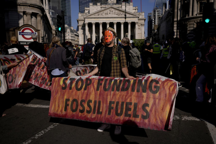 FILE - In this Thursday, Sept. 2, 2021 file photo, an Extinction Rebellion climate change activist holds a banner backdropped by the Bank of England, at left, and the Royal Exchange, center, in the City of London financial district in London. According to a study from University College London climate scientists released on Wednesday, Sept. 8, 2021, strict limits on amounts of fossil fuels extracted from the ground are needed to meet climate goals of the Paris Climate Agreement. (AP Photo/Matt Dunham)