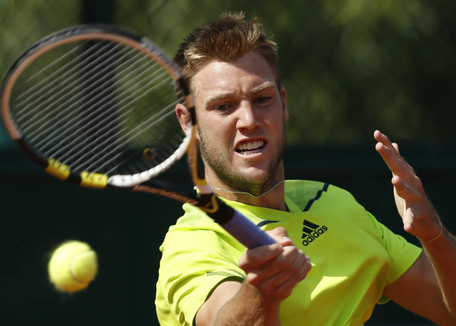 Jack Sock, of the U.S, slams a forehand to Serbia's Dusan Lajovic during their third round match of the French Open tennis tournament at the Roland Garros stadium, in Paris, France, Saturday, May 31, 2014. (AP Photo/Darko Vojinovic)