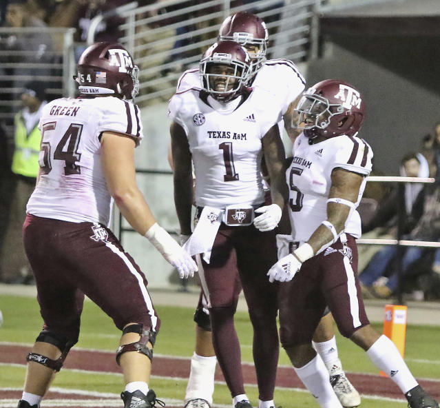 Texas A&M wide receiver Quartney Davis (1) celebrates after scoring a touchdown with teammates Carson Green (54), and Trayveon Williams (5) during the first half of their college football game against Mississippi State Saturday, Oct. 27, 2018, in Starkville, Miss. (AP Photo/Jim Lytle)