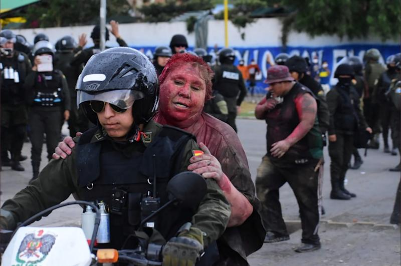 Police rescue Vinto mayor Patricia Arce Guzman on a motorcycle after people threw paint and dirt on her following a fire in Vinto's Town Hall, in Quillacollo, Bolivia, on Nov. 6, 2019. | Daniel James—Los Tiempos Bolivia via Reuters